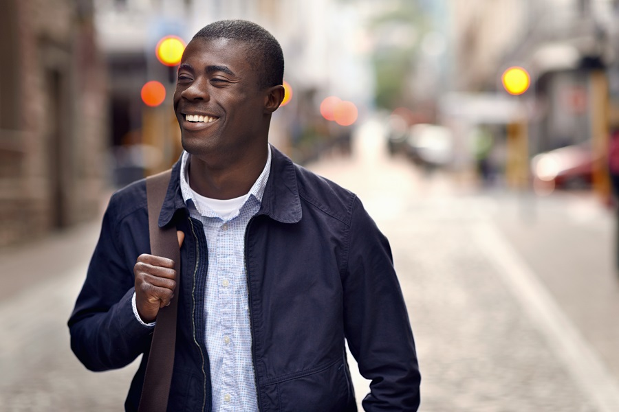 Man smiling while walking down the street