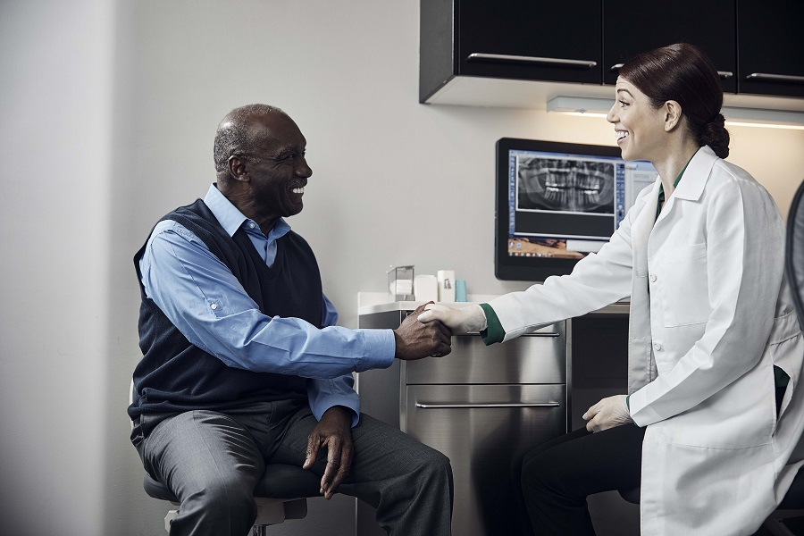 Male patient shaking dentists hand