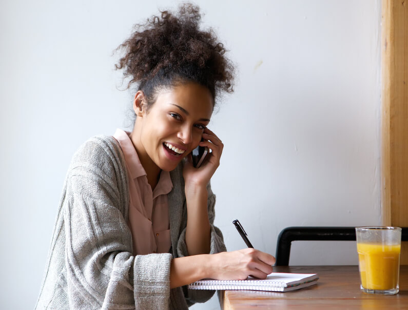 Young woman calling by phone and writing in notebook